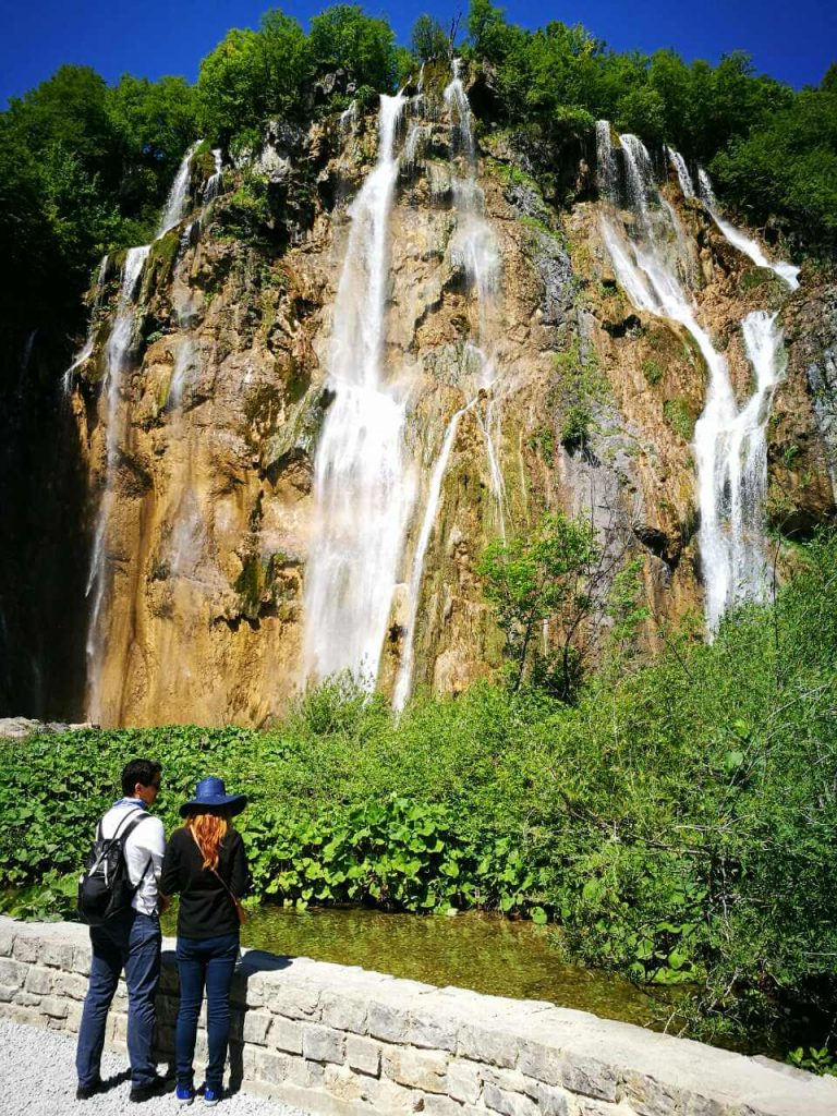 A couple looking at the Great waterfall at Plitvice Lakes in Croatia