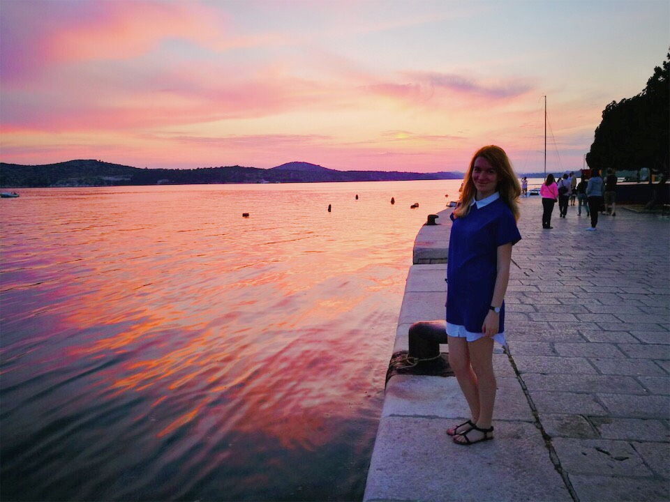 Pink sunset at sea and a pregnant woman smiling