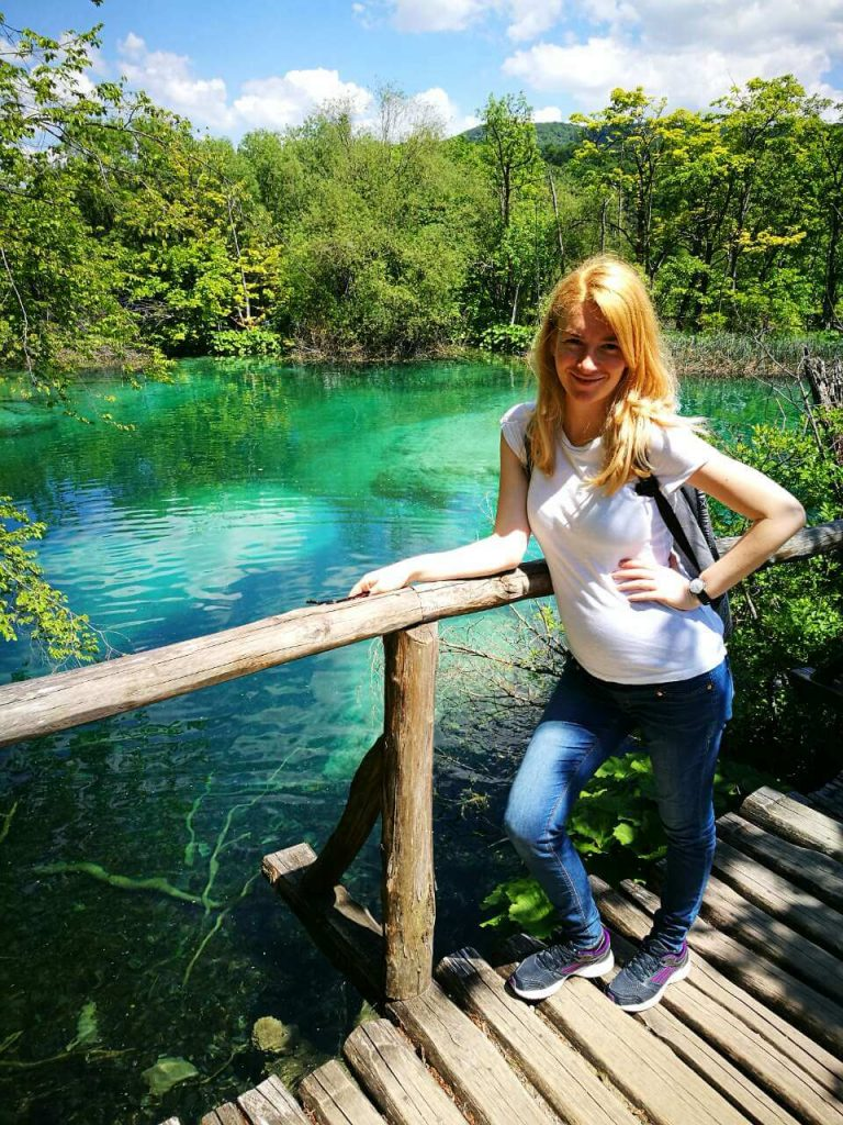 Pregnant woman smiling at Plitvice Lakes in Croatia
