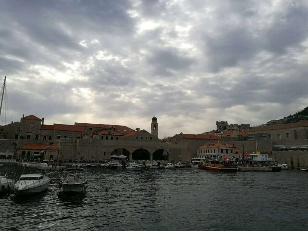 Cloudy sky, city walls and boats at the harbor of Dubrovnik