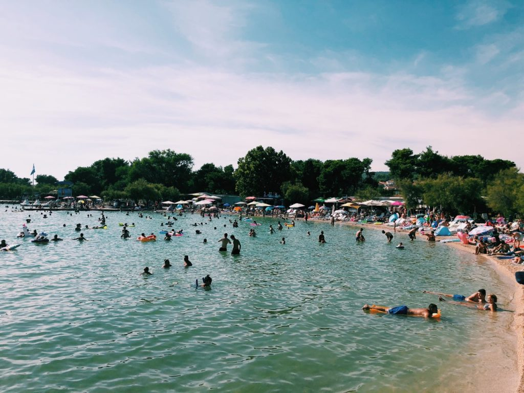 Crowded beach and trees in Vodice, Croatia