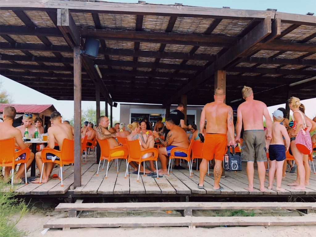 Beach bar with orange chairs full of poeple
