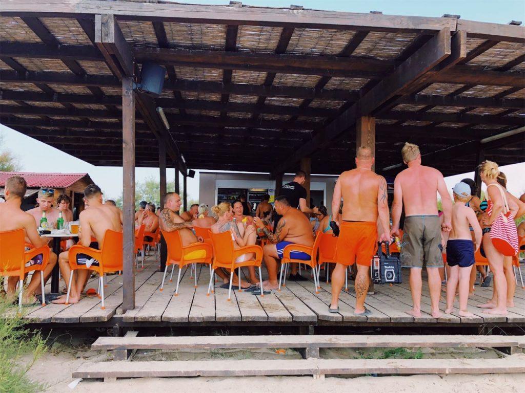 Beach bar with orange chairs full of poeple