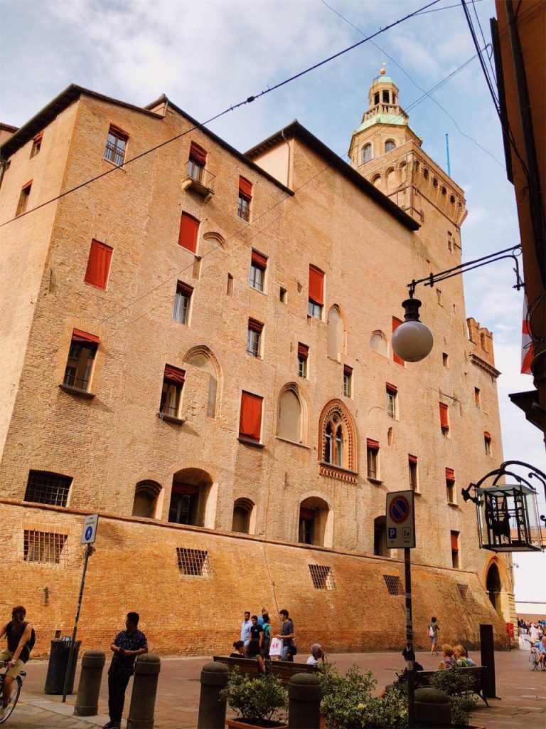 A side view of a brick palace with many windows on Piazza Maggiore in Bologna, Italy