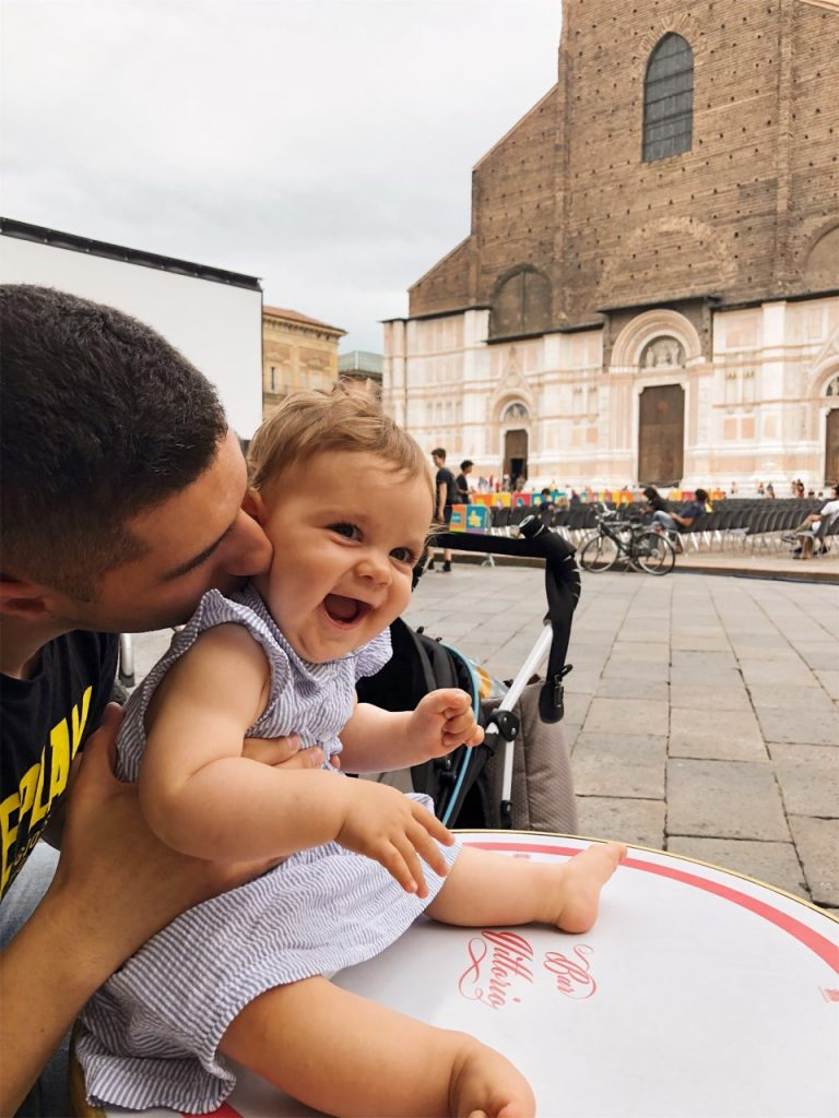 Father kissing baby girl in front of the basilica of San Petronio on Piazza Maggiore in Bologna, Italy