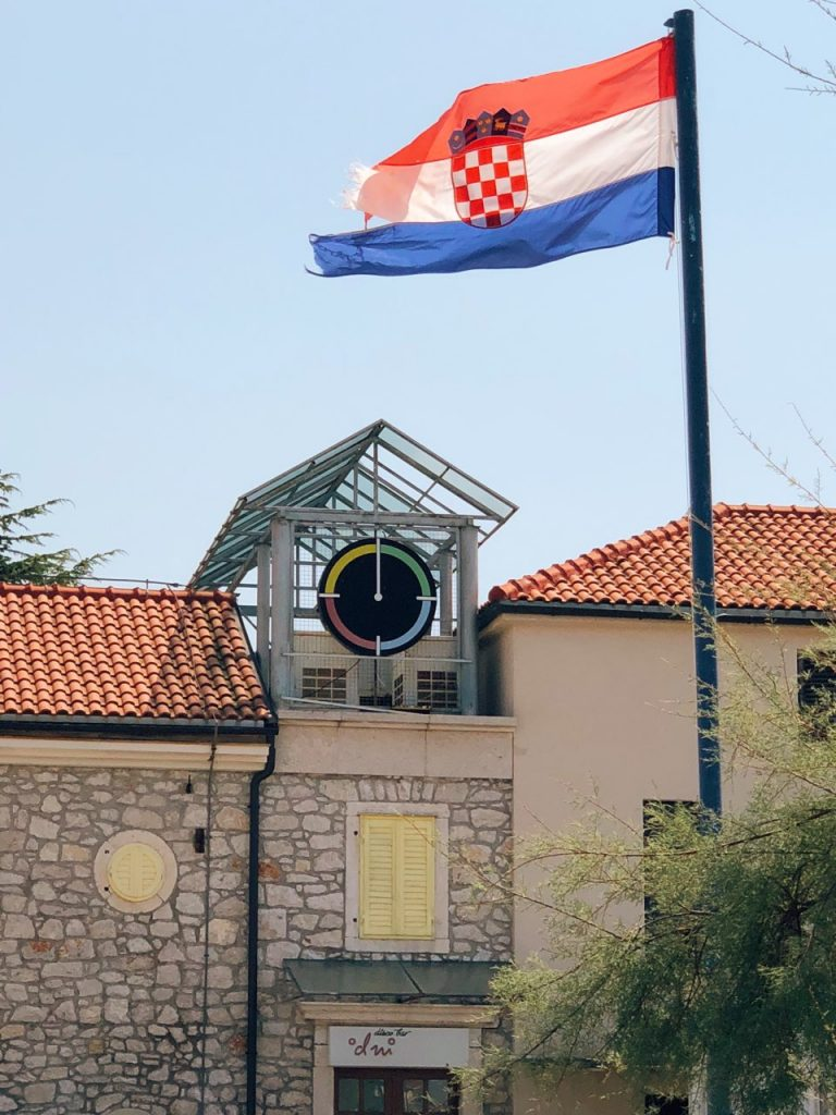 Mediterranean building, clock and the Croatian flag in Zablaće in Croatia