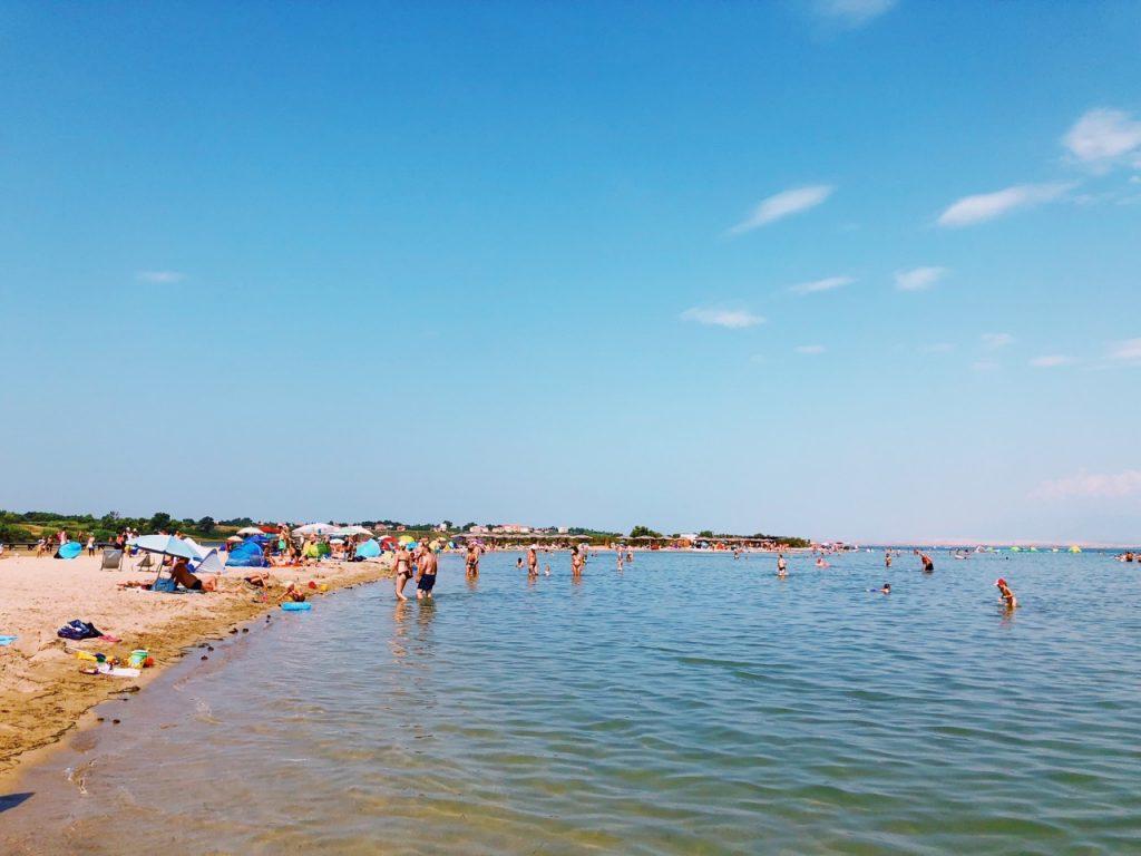 Sandy beach, blue sky and people at Queen's beach in Nin, Croatia
