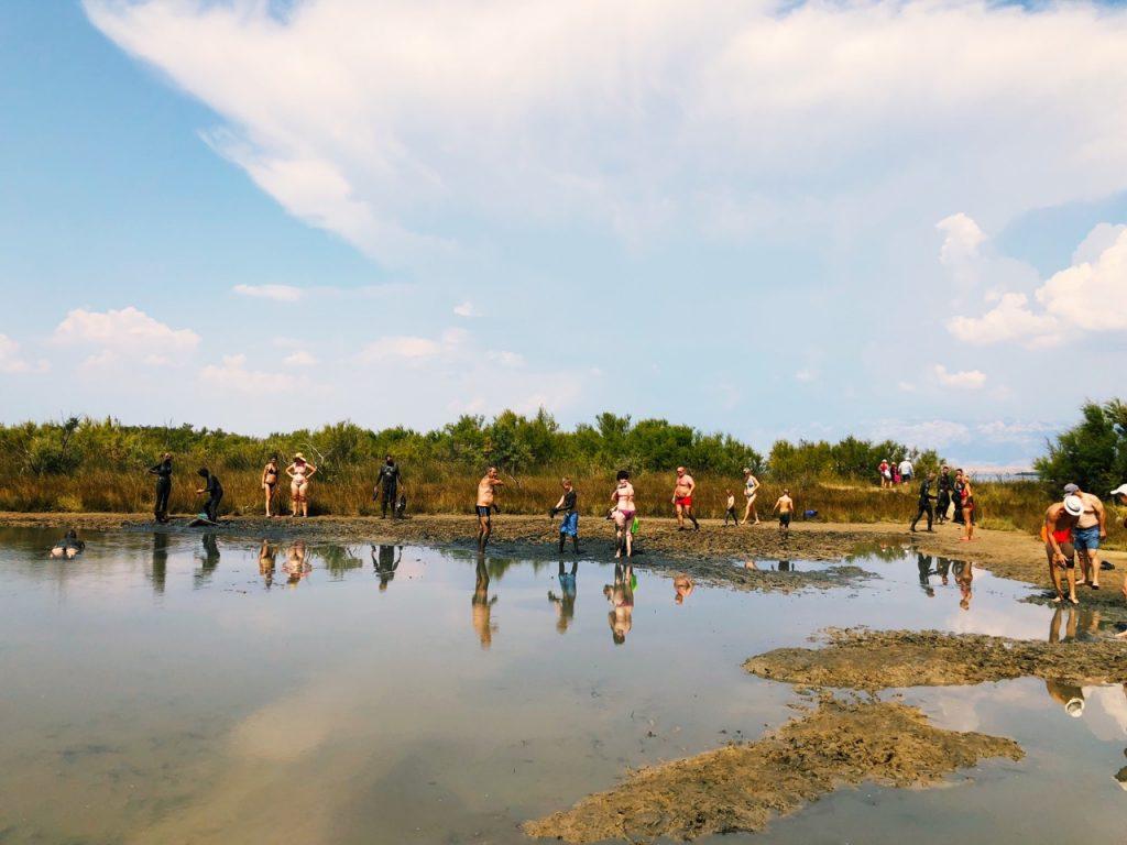 Blue sky and people enjoying medicinal mud at Ninsko blato, Croatia