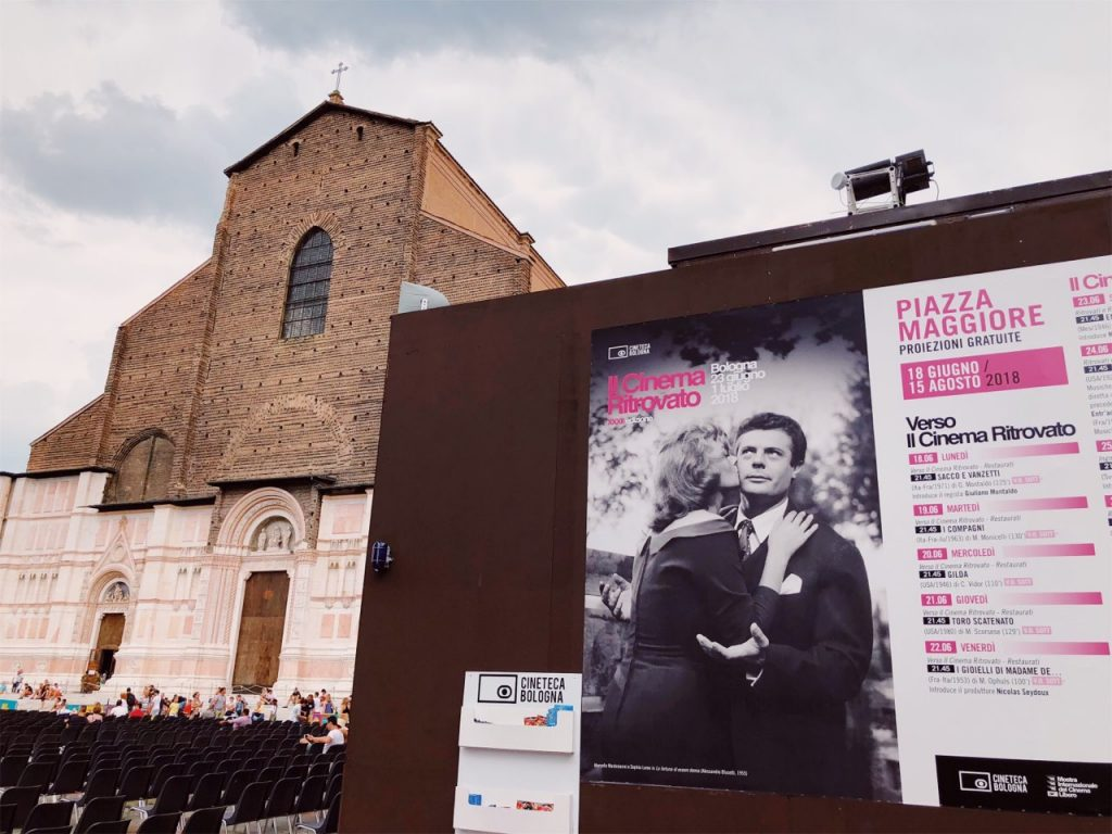 Basilica of San Petronio on Piazza Maggiore and a cinema poster with Sophia Loren and Marcello Mastroianni in Bologna, Italy