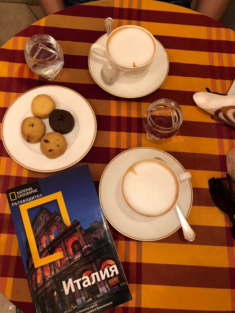 Two cappuccinos, cookies and a book guide of Italy at a table