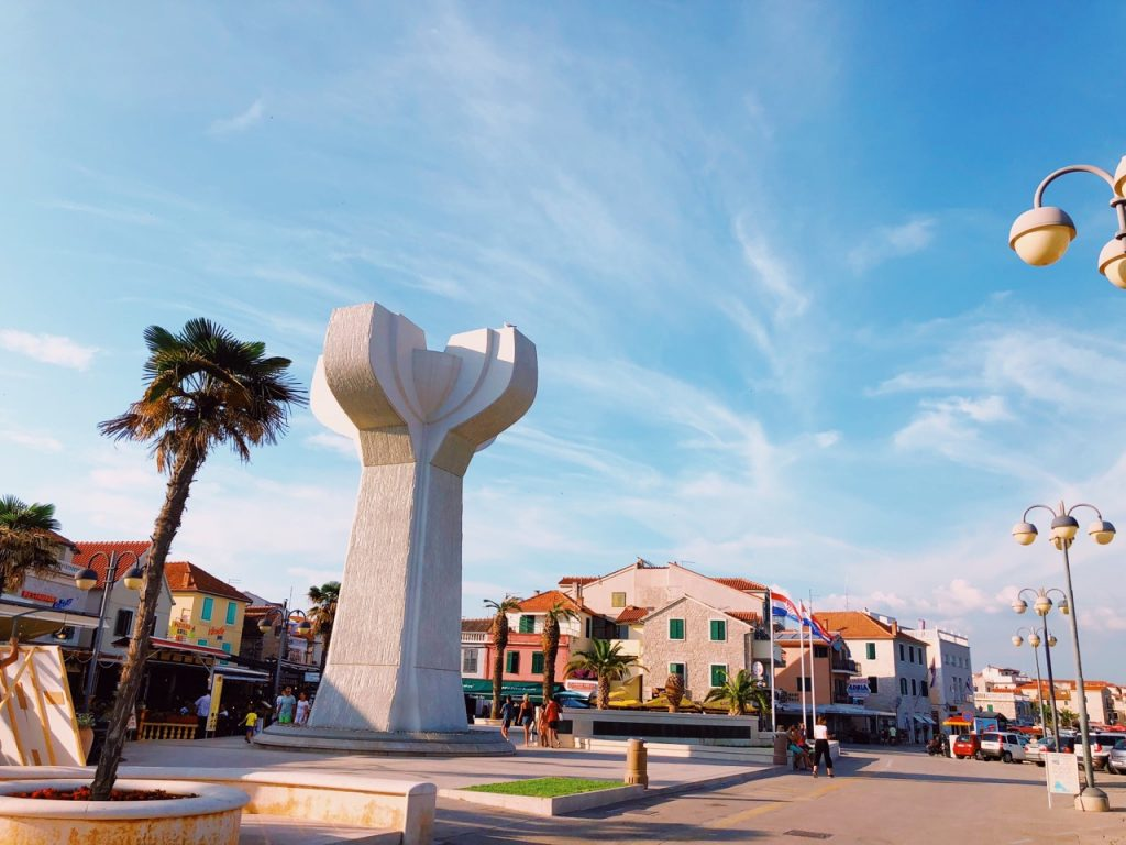 Palm tree, monument and buildings at the main square in Vodice, Croatia