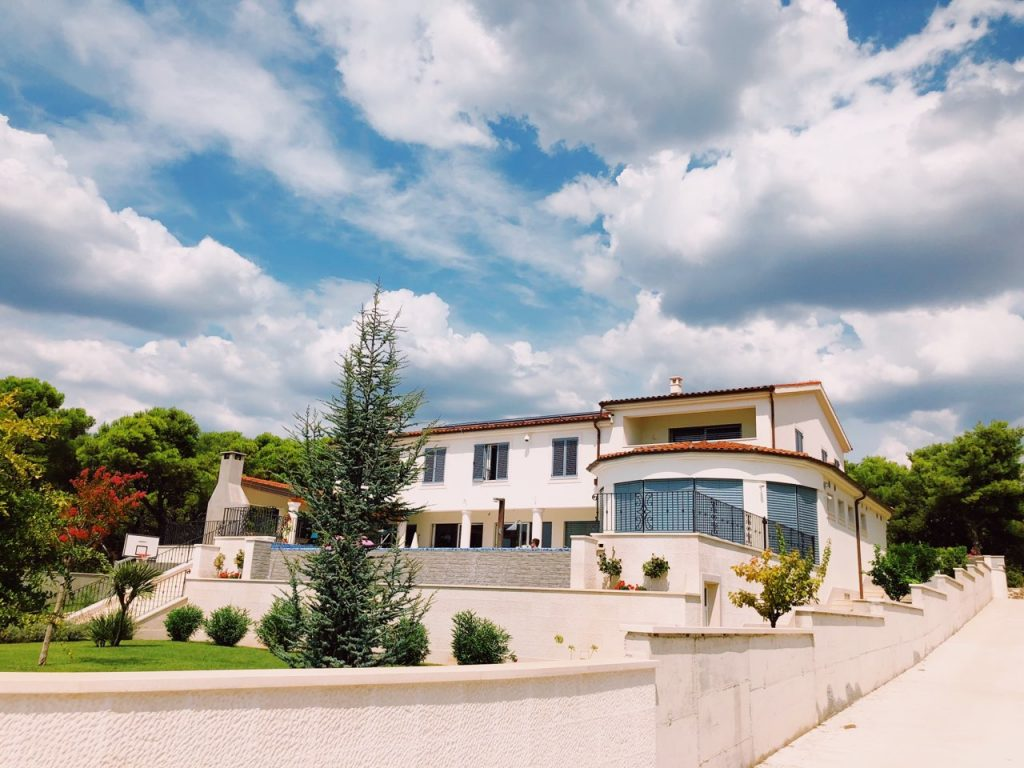 Blue cloudy sky and a two-floor villa in Zablaće in Croatia