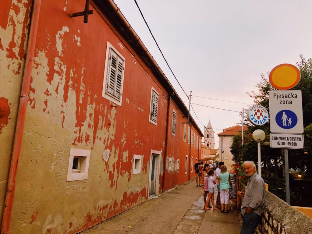 Red Mediterranean building and people on a street in Nin, Croatia