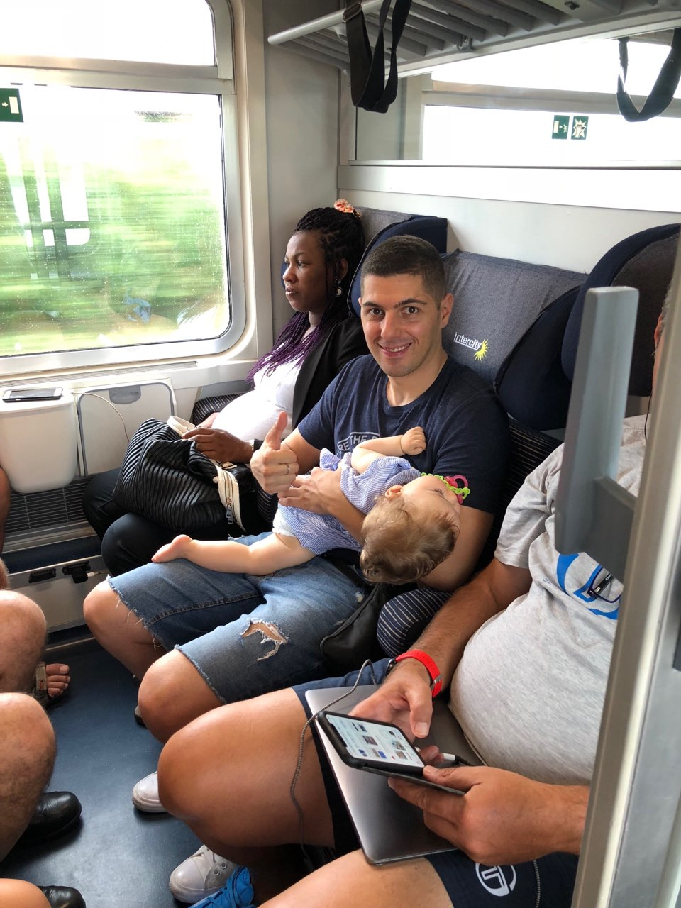 Father, baby girl and passengers on a train in Italy