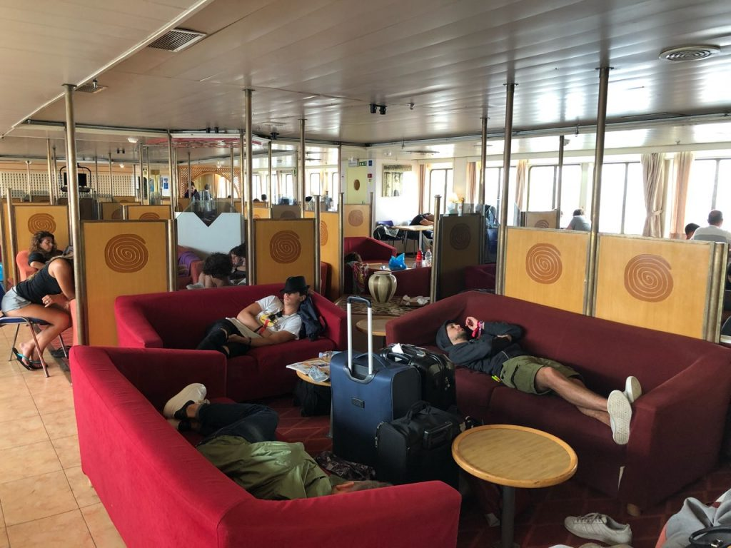 Sleeping passengers on red couches at a ferry from Zadar to Ancona