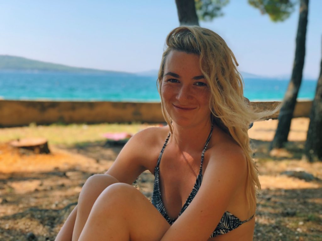 Young blonde woman smiling at the beach at camp Zablaće in Croatia