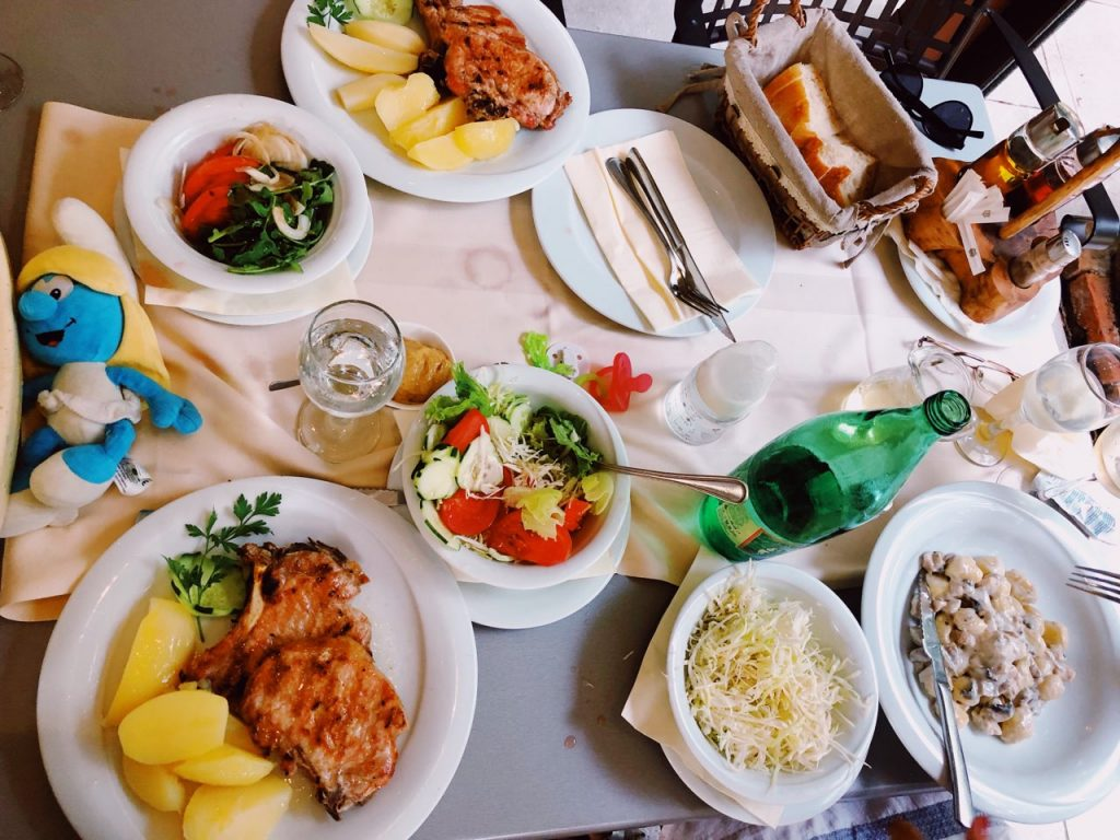 Table with meat meals, salads, water and bread