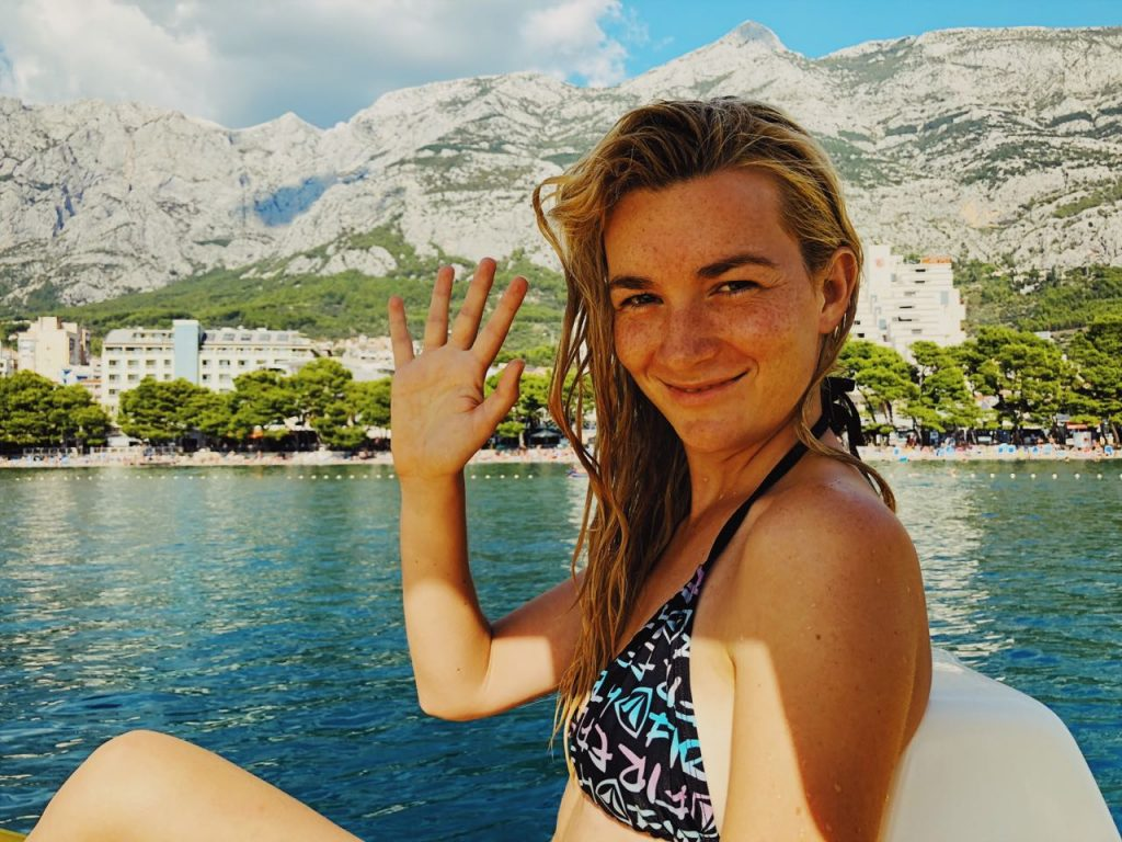 Blonde girl smiling on a boat at the central beach in Makarska, Croatia with Biokovo mountain behind her