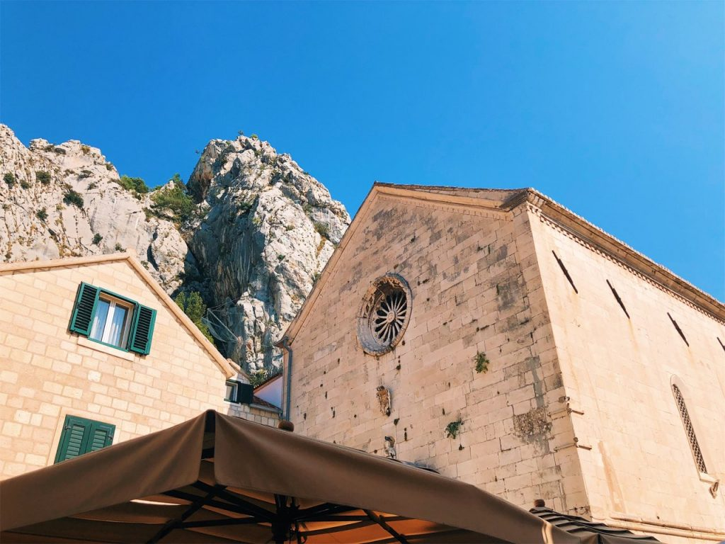 House, church and a rocky mountain in the old town of Omis, Croatia