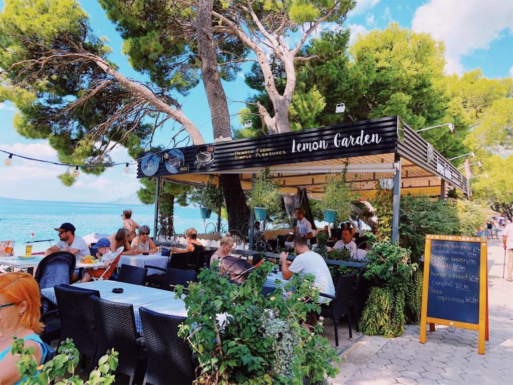 People sitting at restaurant Lemon Garden next to the sea in Makarska, Croatia