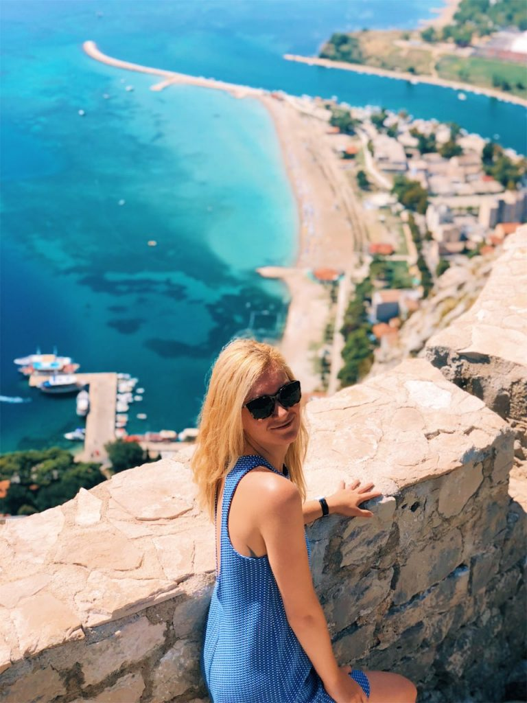 Blonde girl at fortress Starigrad and a view with blue sea in Omis, Croatia