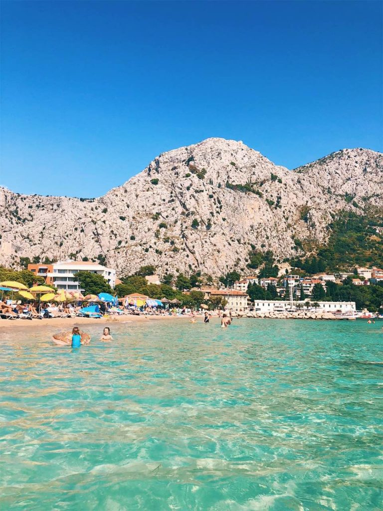 Blue sea water and a rocky mountain at beach Punta in Omis, Croatia