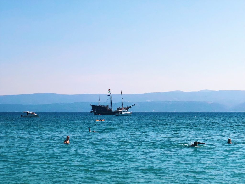 Oldschool ship and blue sea water at beach Punta in Omis, Croatia