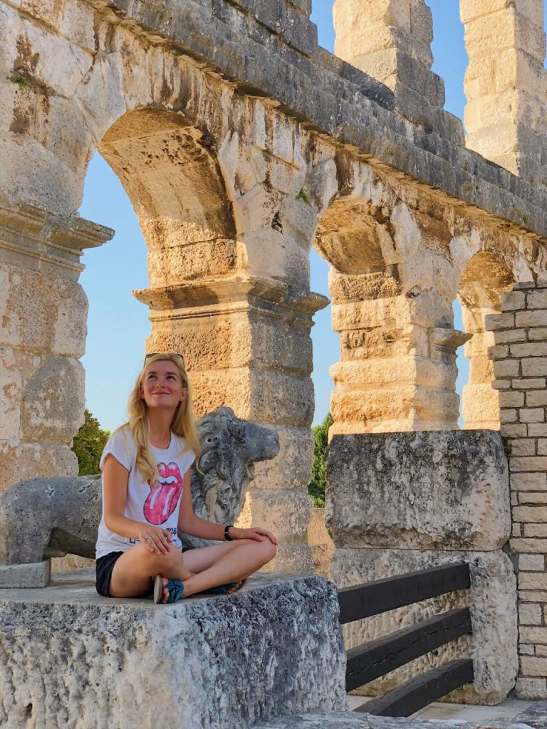 Young woman sitting at Pula Arena in Pula, Croatia