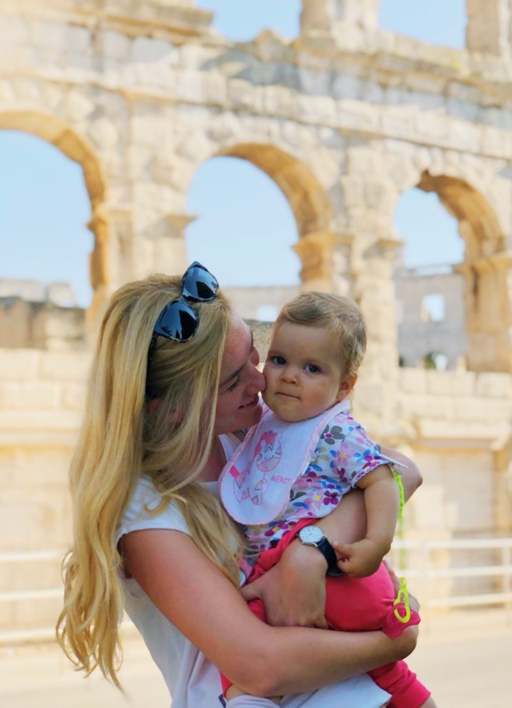Mother and baby girl in front of Pula Arena in Pula, Croatia