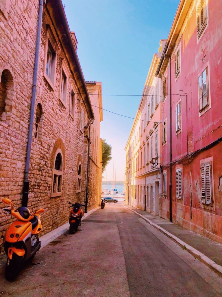 Sea view between stone and colorful buildings in Pula, Croatia