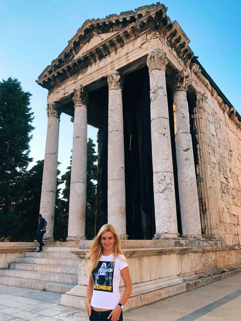 Young woman in front of the temple of Rome and Augustus at the center of Pula, Croatia
