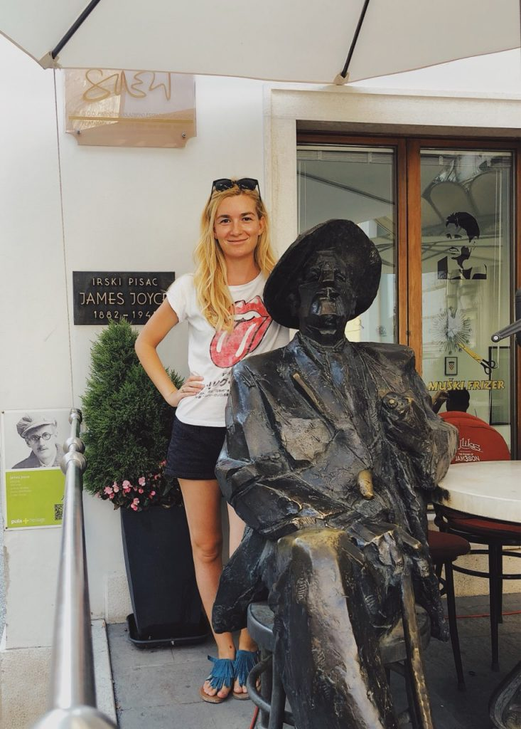 Young woman with a statue of James Joyce in Pula, Croatia