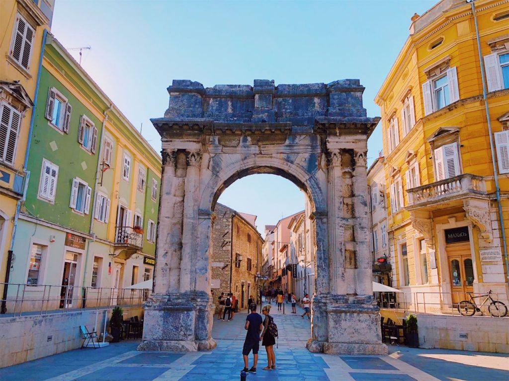 Colorful Mediterranean buildings and the Arch of the Sergii in Pula, Croatia