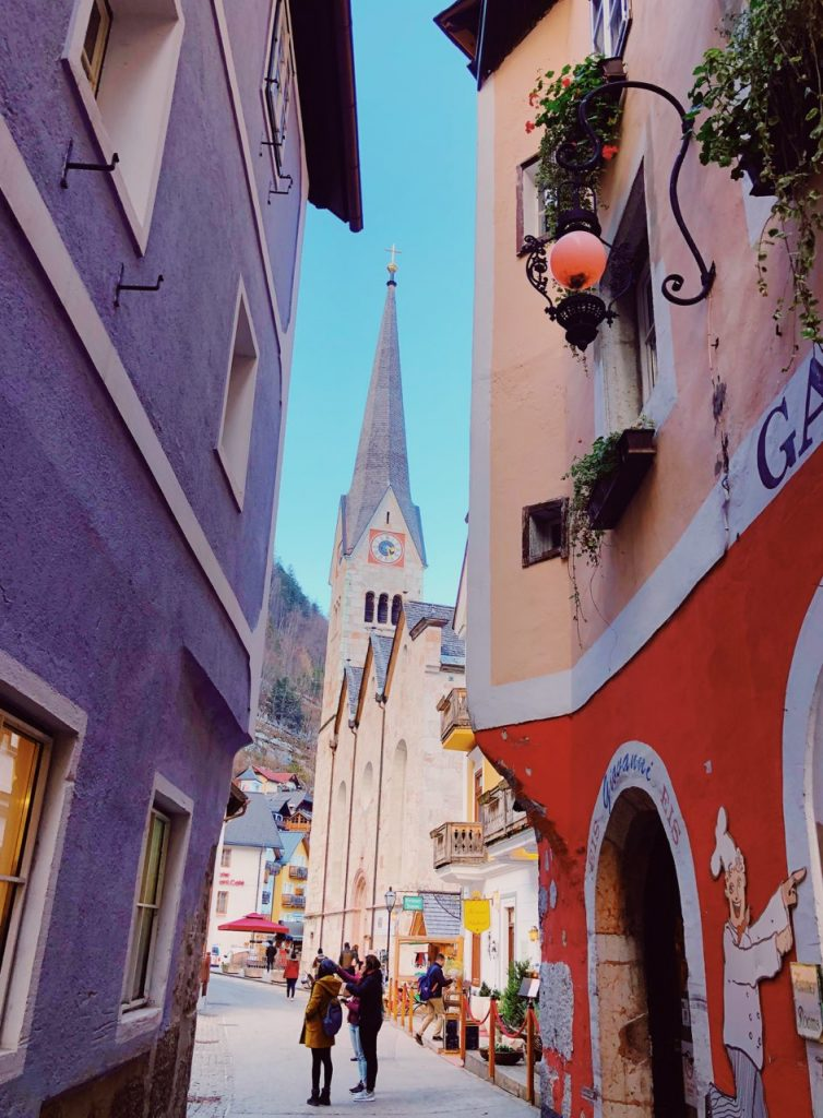 Colorful buildings and a church tower nehind them in Hallstatt