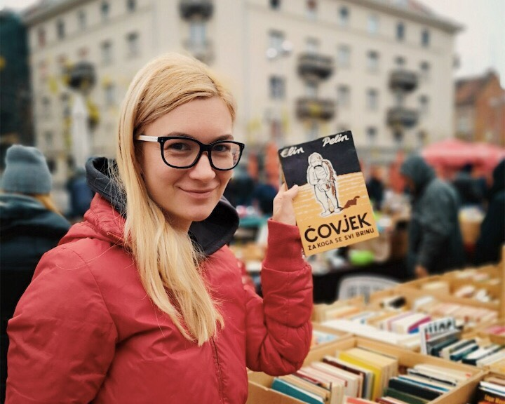 Blonde woman with glasses holding a book