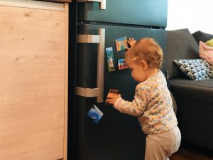 baby girl playing with magnets on the fridge