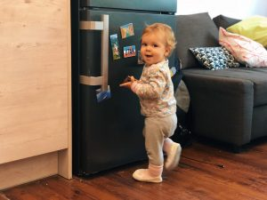baby girl smiling and playing with magnets on the fridge