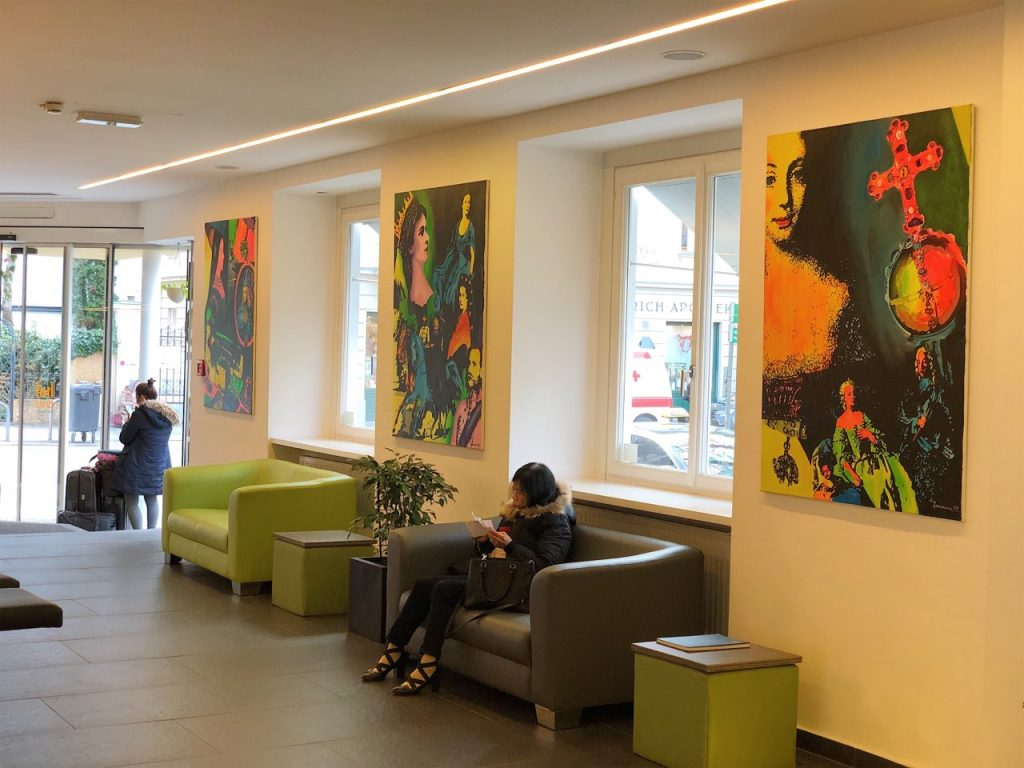 Hotel lobby with three colourful poctures on the wall