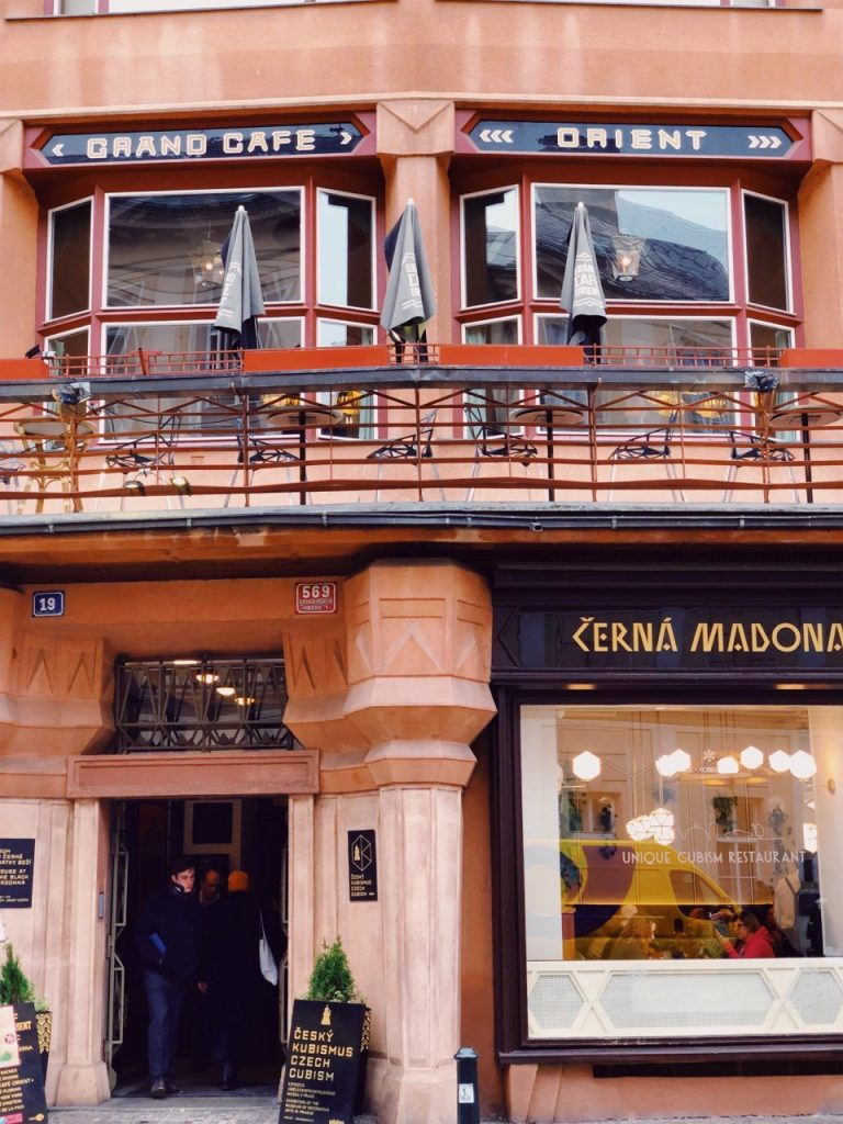 The entrance to the House of the Black Madonna and the balcony of Grand Cafe Orient in Prague