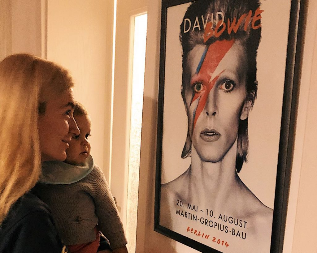 Mother and baby next to David Bowie poster