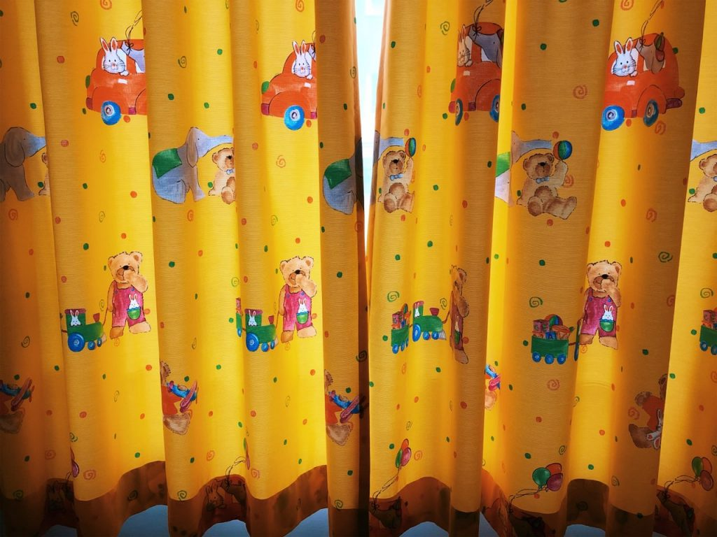 Orange curtains with animals and means of transportation