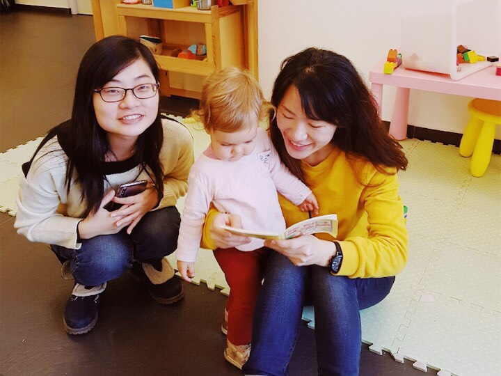 Two girls reading to a baby