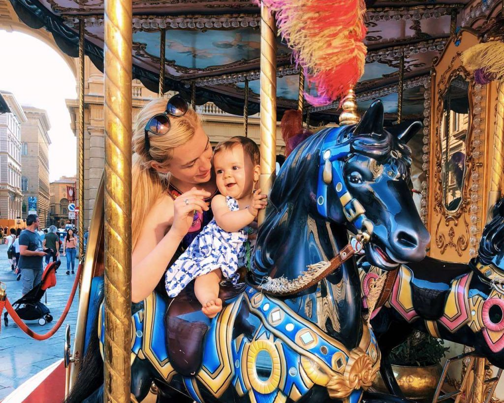 Mother and baby girl at the carousel in Florence