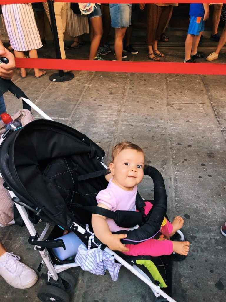 Baby girl in pink waiting to get in Uffizi in Florence